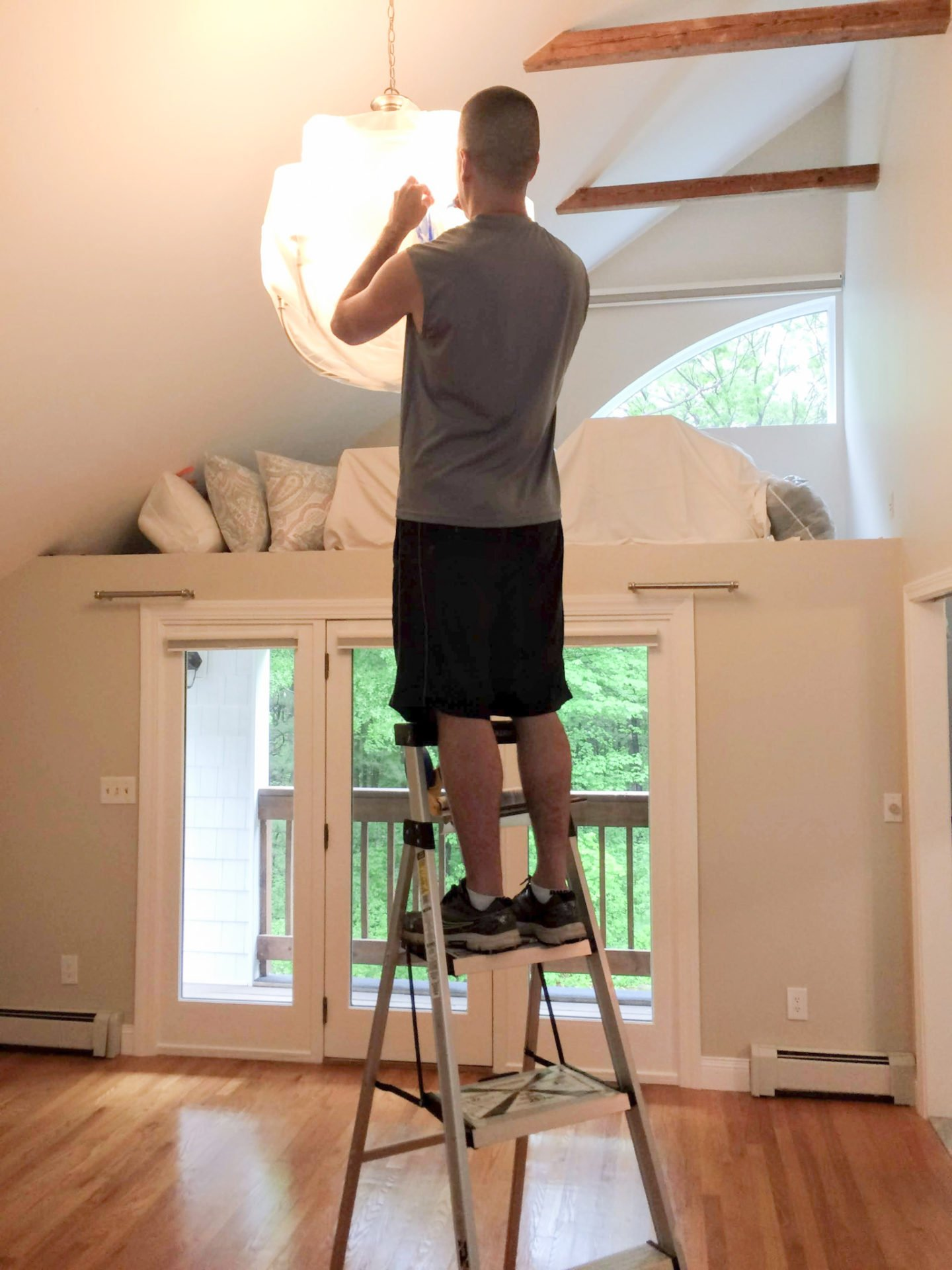 My husband wrapping our lighting fixtures with masking film for easier clean-up