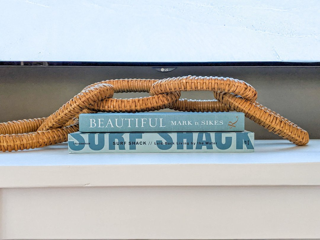 These blue coffee table books and wicker chain link give this TV console more of a coastal look
