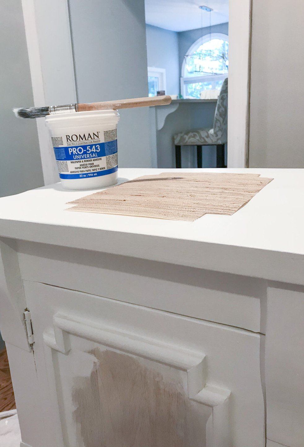 One of the final steps in this grasscloth furniture tutorial is to apply the grasscloth using wallpaper adhesive